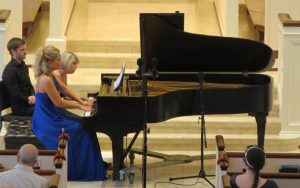 "Julie Coucheron (left) and Elizabeth Pridgen perform the ""four hands"" piano piece. (Photo by Mark Gresham)"