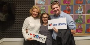 "Julie and David Courcheron with Lois Reitzes holding posters with the text ""City Lights"""
